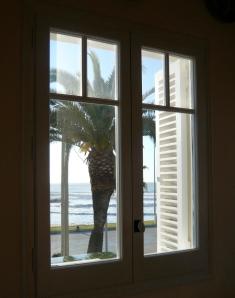 Finestra amb palmera i mar de fons. Fot. Frèia Berg